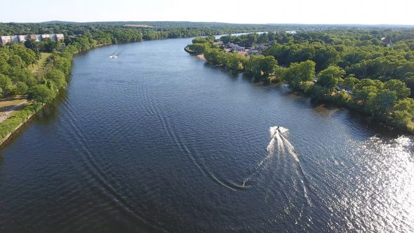 Aerial Drone Video of Jet Skis on A River Pan Out