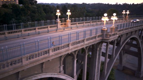 Girl Rides Bicycle Over Bridge Royalty Free Stock Drone Video Footage