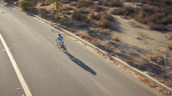 Hillside Suburb Cyclist 1 Royalty Free Stock Drone Video Footage